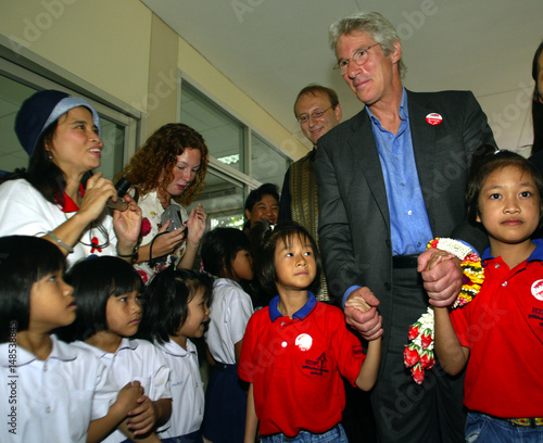 ACTOR AND AIDS ACTIVIST RICHARD GERE HOLDS HANDS OF ORPHANS WHILE VISITING THE MERCY CENTRE IN BANGKOK.
