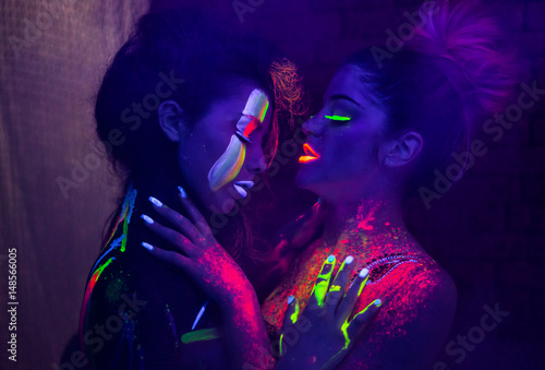 Fotomural Sexy lesbian models in uv neon light with fluorescent glowing Body Art make-up