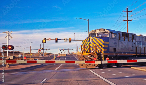 A train crosses a busy street at a railroad crossing