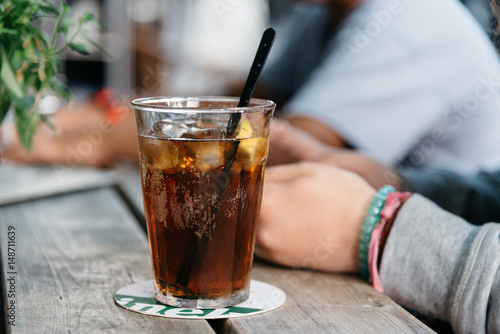Refreshing glass of cola on wooden table in a bar Fototapet