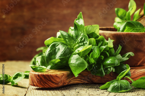 Papiers peints Condiment Fresh green basil in olive mortar with pestle, vintage wooden background, rustic style, selective focus