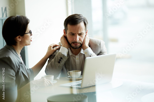 Fotografia  Tense businessman looking at laptop display while colleague comforting him