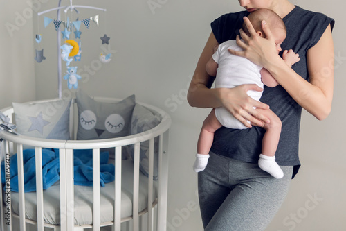 Photo mother sleeping on the chest of his son is at round bassinet at home