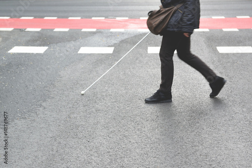 Blind person walking with a stick crossing a pedestrian walkway Fototapet