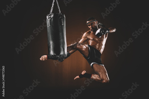 side view of focused muay thai fighter practicing kick on punching bag, action sport concept