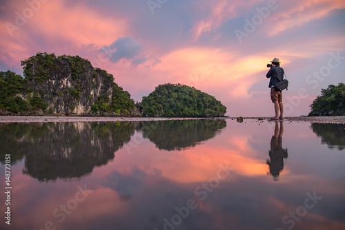 Reflection of man photographer take photo of summer landscape with beautiful sunset sky at Ao Nang Beach, famous tourist attraction and travel destination of Krabi Province, Thailand