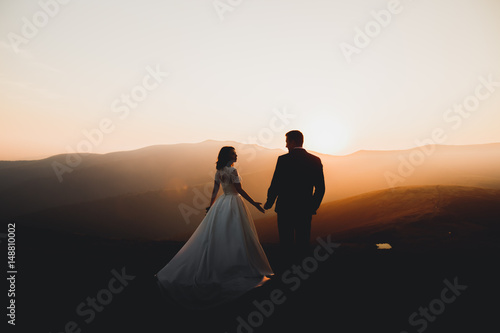 Obraz Wedding couple posing on sunset at wedding day. Bride and groom in love - fototapety do salonu