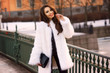 Happy joyful girl in white fur coat holding black leather handbag and walking down the street on a cold winter evening at sunset