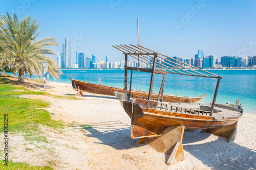 Poster de jardin Abou Dabi Wooden boat at the Heritage Village, in front of the Abu Dhabi skyline, United Arab Emirates