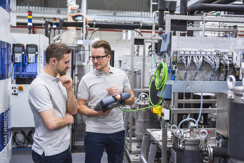 Two men with control in factory shop floor