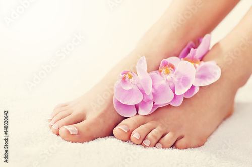 In de dag Pedicure Soft female feet with french pedicure and flowers close up