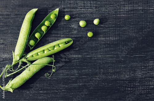 Pods of green peas on a dark wooden surface, top view
