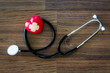 Stethoscope with red heart on wooden background