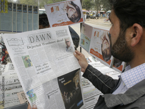 A man reads a newspaper with the news of Pakistan's cricket