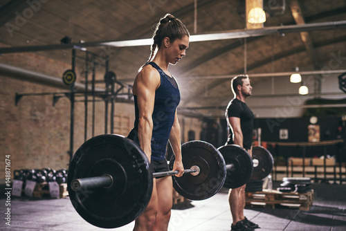 Foto op Aluminium Fitness Sportive serious people lifting barbells in gym