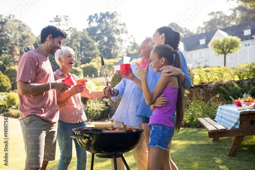 Photo sur Toile Grill, Barbecue Family laughing and talking while preparing barbecue in the park