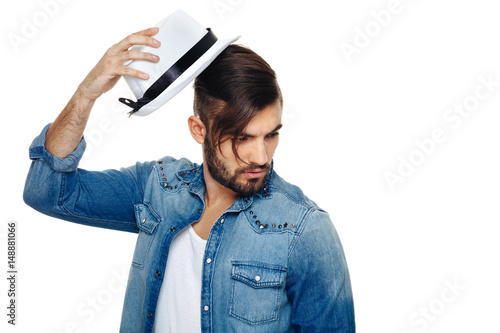 Obraz na plátně  Bearded man with a hat posing in the studio