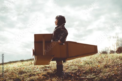 front view vintage pilot boy flight by imagination on cardboard plane outdoor Wallpaper Mural