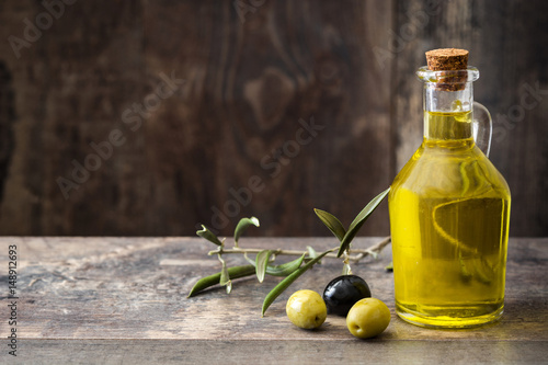 Virgin olive oil in a crystal bottle on wooden background.Copyspace