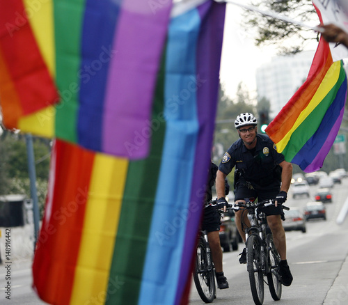 A Beverly Hills police officer cycles past flags during a rally