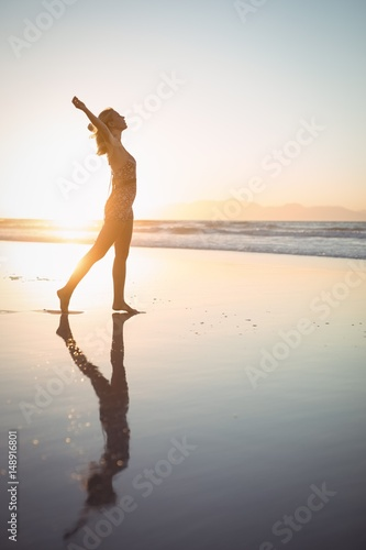 Photo  Side view of carefree woman with arms outstretched at beach
