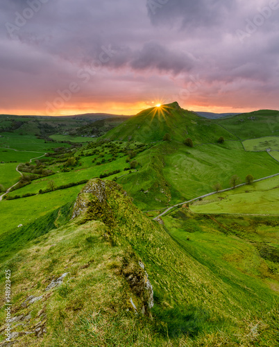 sun-shining-brightly-as-it-sets-below-horizon-at-sunset-with-chrome-hill-in-the-background-taken-in-the-peak-district-national-park-uk