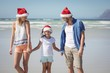 Happy family wearing Santa hat while standing at beach