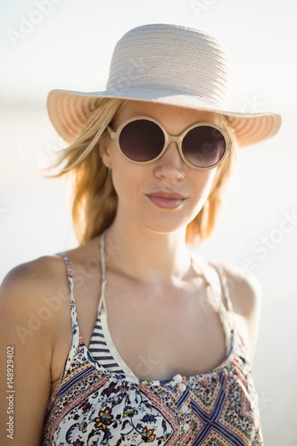 48f0230165 Portrait of young woman wearing sunglasses and hat at beach - Buy ...