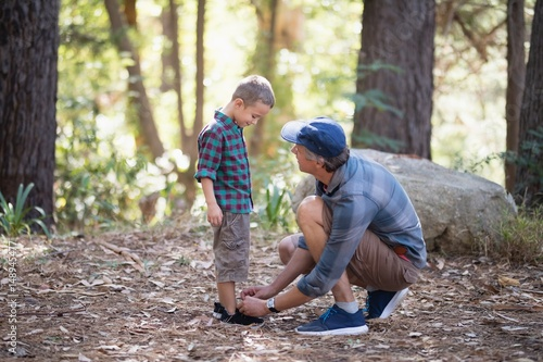 Fotografía  Father tying shoelace of son in forest