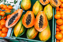 Bright And Juicy Appetizing Sliced Papaya And Other Exotic Fruits On The Counter Of The Street Market