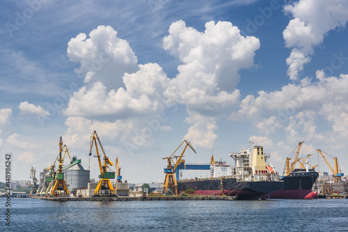 Scenic view with cumulus clouds above industrial seaport with large freighters docked for shipping in Constanta, Romania.