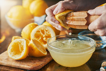 Squeezing Fresh Lemon Juice With Wooden Reamer Into Bowl