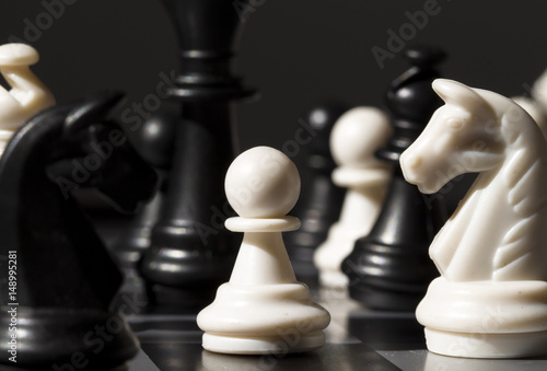 Fotografie, Obraz  White pawn between black figures on chessboard