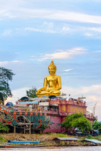 Beautiful Golden Buddha Statue Of Phra Buddha Nawa Lan Tue On The Banks Of The Mekong River At Golden Triangle Park (Sob Ruak) During The Evening In Chiang Rai Province, Thailand