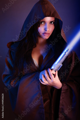Photo  Beautiful girl holding a lightsaber
