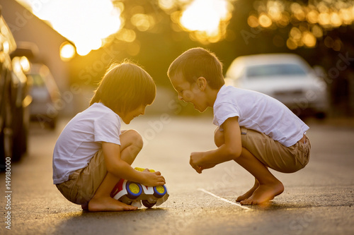 Photo  Two sweet children, boy brothers, playing with car toys on the street in village