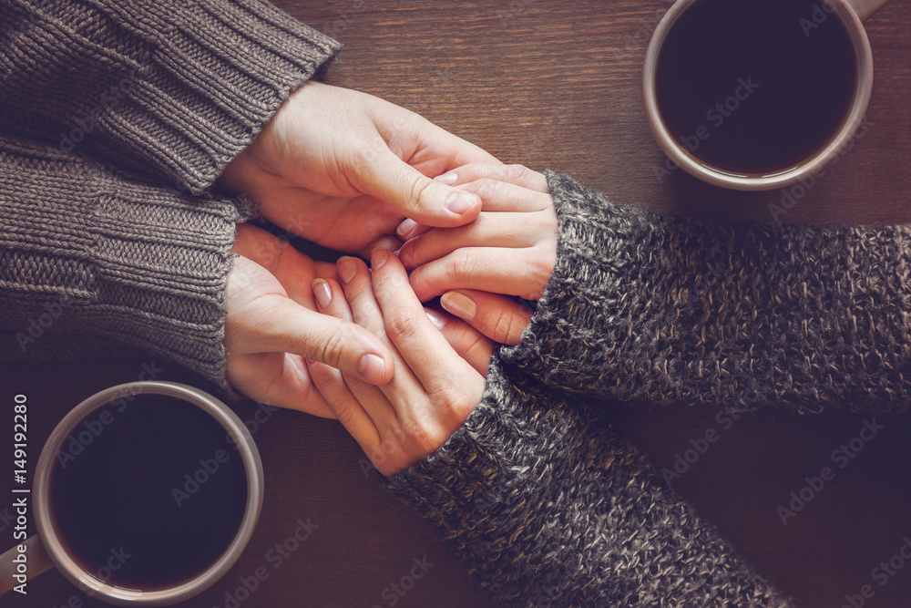 Fototapety, obrazy: Man holding woman's hands. Young couple enjoying coffee and lovely conversations in the romantic evening atmosphere.