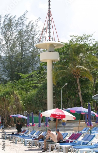 Tourists relax in front of tsunami warning tower at Patong