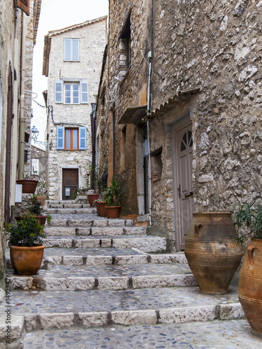 Fototapeten Schmale Gasse SAINT-PAUL-DE-VENCE, FRANCE, on JANUARY 9, 2017. Ancient stone buildings make architectural appearance of the typical medieval French town in the Alps