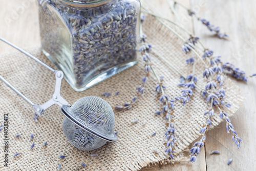 Dry lavender tea in tea infuser spoon and glass jag on wooden background, horizo Tapéta, Fotótapéta