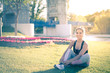 sports woman doing lawn exercises and stretching on the grass outdoor in a park listening music