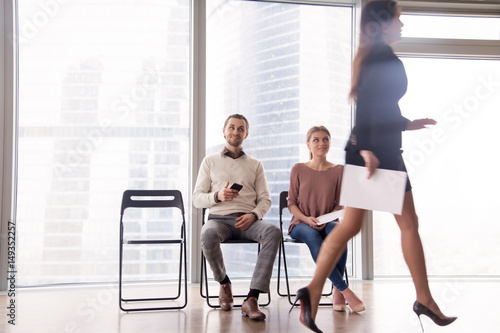 Fototapety, obrazy: Unhappy attractive businesswoman walking by male and female job candidates sitting on chairs, gazing at her and smiling, gloating over unfortunate competitor, beating rival, competing for position