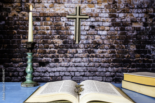 three bibles on blue table one open with reading glasses and lit candle in antique candle holder with wooden cross on brick wall background