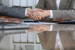 Group of business people or lawyers at meeting shaking hands, close up