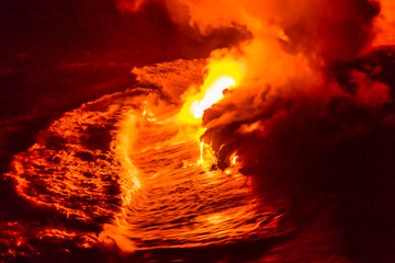 Lava flow pouring into Hawaii ocean at night. Lava falling in ocean waves in Hawaii from Hawaiian Kilauea volcano at night. Molten lava washed by the pacific ocean water crashing in, Big Island, USA.