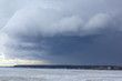 Winter ice Sea view. Stormy dramatic sky. Dark, Ominous Rain Clouds