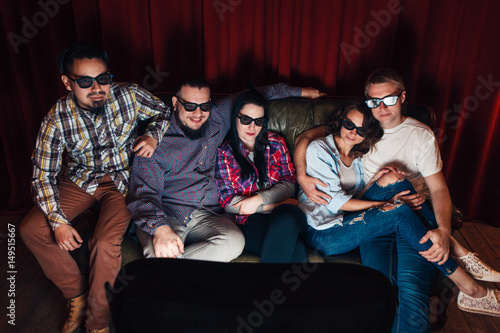 Company of five young happy people in 3d glasses watch tv at home