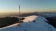 Flying over communications tower, mountain snow covered winter landscape.