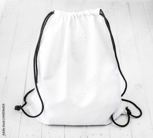 Obraz white backpack with black string on planked surface - fototapety do salonu