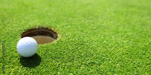 Tuinposter Golf golf ball on lip of cup